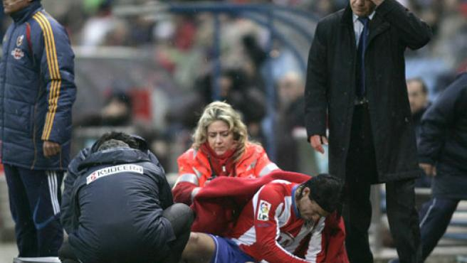 El Kun Agüero recibe asistencia médica tras caer lesionado. (EFE)