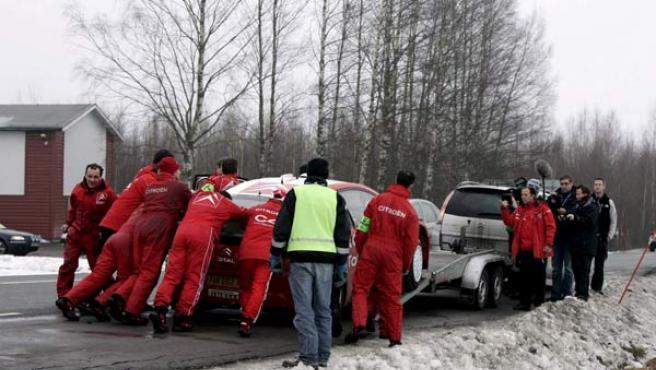 Miembros del equipo Citroen empujan el coche del francés Sebastien Loeb tras su accidente sufrido en Suecia. (MICKE FRANSSON /EFE)