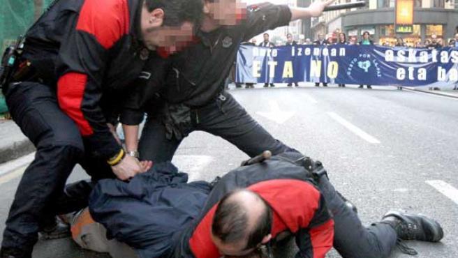 Agentes de la Ertzaintza reducen a un hombre que ha increpado a los manifestantes. (EFE)