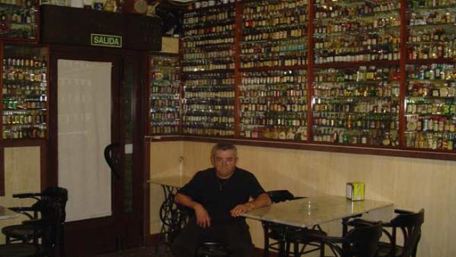 Manuel Morales, rodeado por las botellitas que colecciona en su bar.
