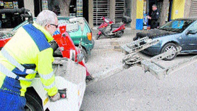 Una grúa preparada para retirar, ayer, un coche aparcado en una parada de taxi.(Fernando Muñoz)