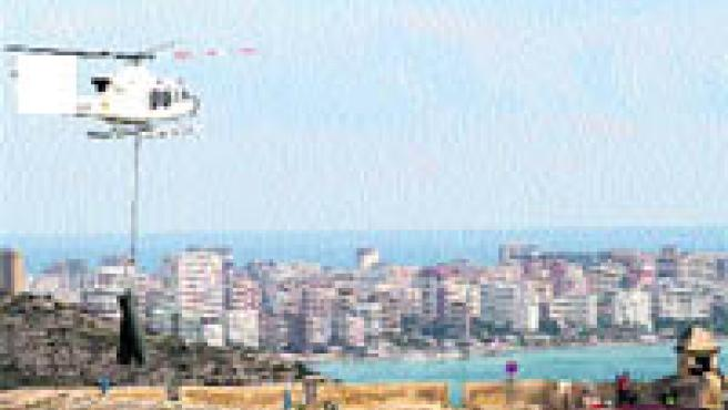 Un helicóptero traslada varios rollos de malla hasta la cima del Benacantil, ayer (F. González).