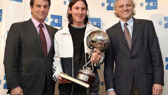 El delantero argentino del Barcelona, Lionel Messi (c) posa con el trofeo EFE junto al presidente del club azulgrana, Joan Laporta (i) y junto al presidente de la agencia, Alex Grijelmo. (ANDREU DALMAU / EFE)