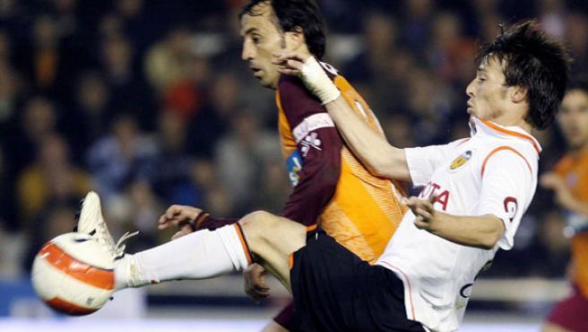 El delantero del Valencia David Silva lucha un balón con el defensa del Recreativo de Huelva Quique Álvarez. (efe)
