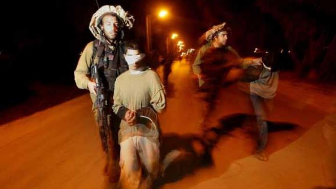 Soldados israelíes llevan detenidos a jóvenes palestinos en la anterior incursión en Gaza. (REUTERS)
