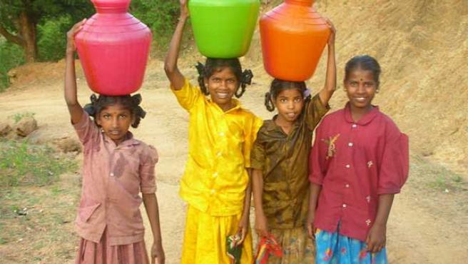 Un grupo de niñas indias lleva tres cántaros de agua. (WIKIMEDIA)