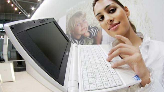 Una joven muestra el portátil de Asus