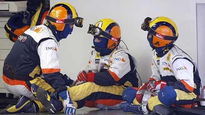 Mecánicos del equipo Renault conversando en el box.