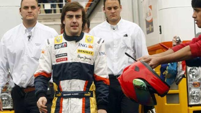 Fernando Alonso es escoltado por dos empleados de seguridad del circuito de Montmeló (REUTERS).