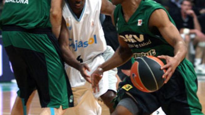 El jugador del DKV Joventut Demond Mallet (d) trata de escapar de Elmer Bennet (c), del Cajasol Sevilla. (EFE)
