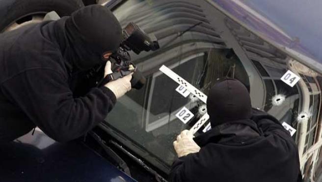 Dos policías toman fotografías del coche donde se encontraba el ex edil.(REUTERS)
