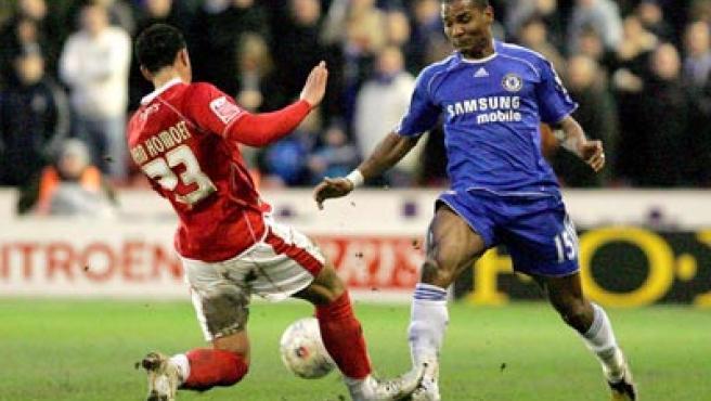 El jugador del Chelsea Florent Malouda lucha por el balón con Marciano Van Homoet, del Barnsle