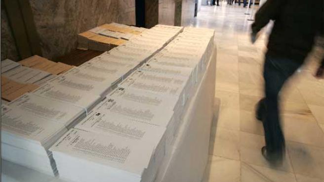Una personas pasa junto a una mesa con las papeletas de votación en el colegio San Agustín de Madrid.(EFE)