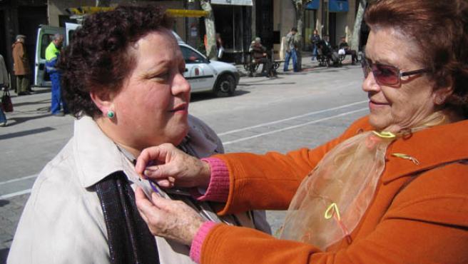 Una participante asistente a la celebración coloca lazos conmemorativos