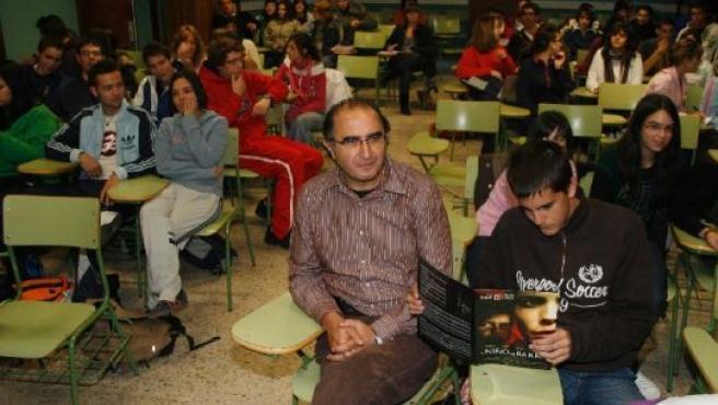 Un profesor en clase junto a sus alumnos.
