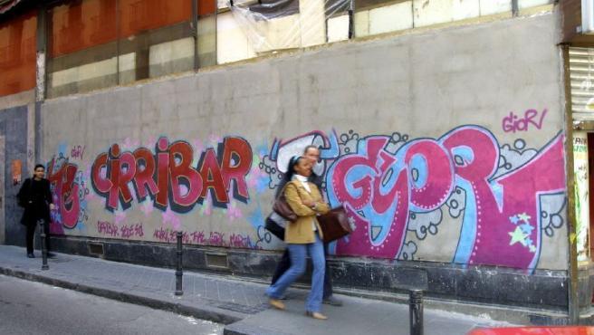 Unos peatones caminan junto a un grafitis.