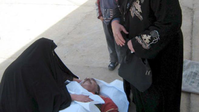 Una iraquí llora sobre el cadaver de un familiar en la morgue de un hospital en Bagdad (Irak). (Ali Mohammed/EFE)