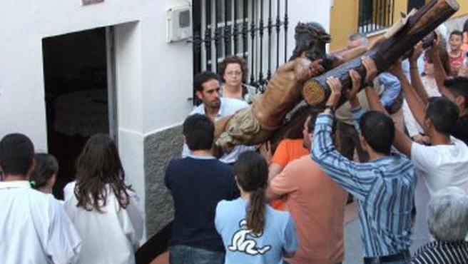 Los costaleros con el crucificado frente a un domicilio del Tesorillo.