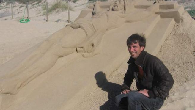 Sergi Ramírez, ganador del I Encuentro Internacional de Escultores de Arena, junto a su obra, 'cricificado'.