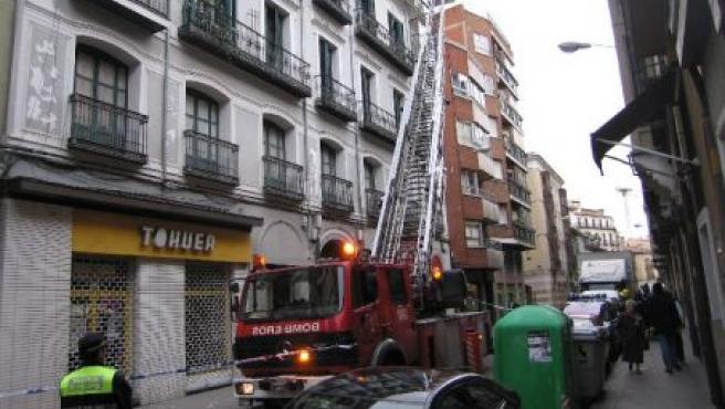 Los bomberos intentan tirar el resto de escombros que cuelgan del edificio de Claudio Moyano.