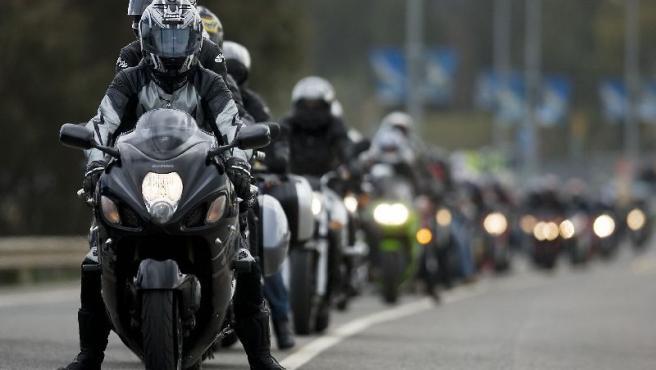 Aficionados al motociclismo hacen cola, sobre sus motos, para entrar en el Circuito de Jerez.