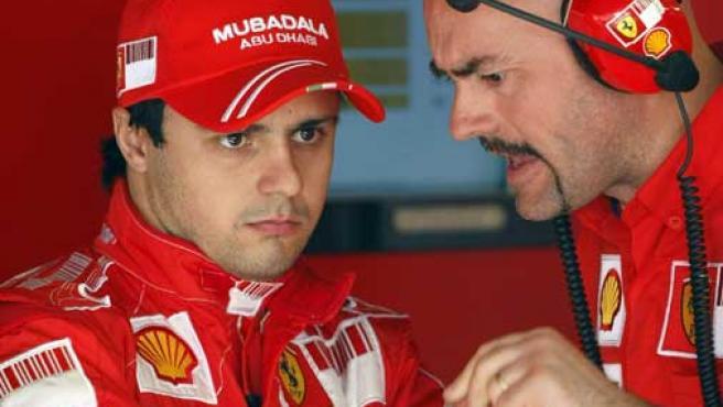 Felipe Massa escucha las indicaciones de un mecánico de Ferrari en Montmeló (REUTERS).