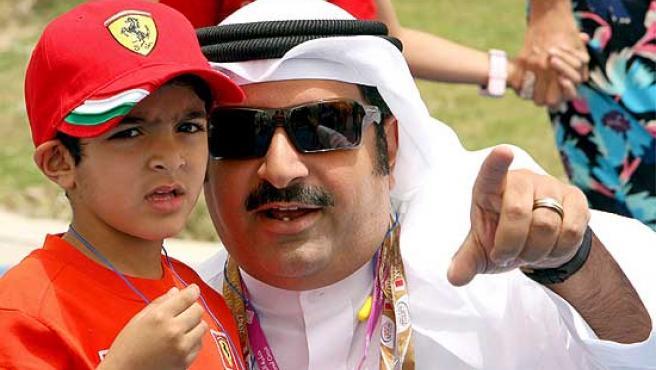 Un aficionado de Ferrari acude con su hijo al circuito de Sakhir.