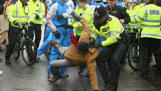 Agentes de seguridad bloquean al manifestante que trató de arrebatar la antorcha olímpica a la presentadora británica Konnie Huq. (Efe)