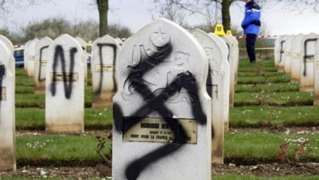 Algunas de las tumbas del cemeterio de Arras, profanadas con símbolos y eslóganes nazis (FOTO: AP)