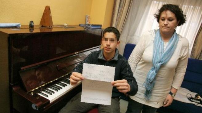 Karim, junto a su madre, muestra la cita del médico. (JORGE PARÍS)
