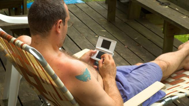 Un hombre juega con una Nintendo DS