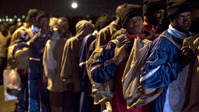 Inmigrantes esperando en fila en el puerto de Los Abrigos (Tenerife). SANTIAGO FERRERO / REUTERS