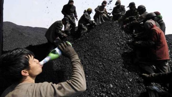 Un trabajador bebe cerveza mientras otros buscan carbón. (REUTERS/Stringer)