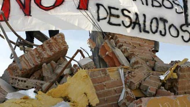 Varios jóvenes muestran una pancarta sobre una vivienda derribada durante la manifestación. (EFE)