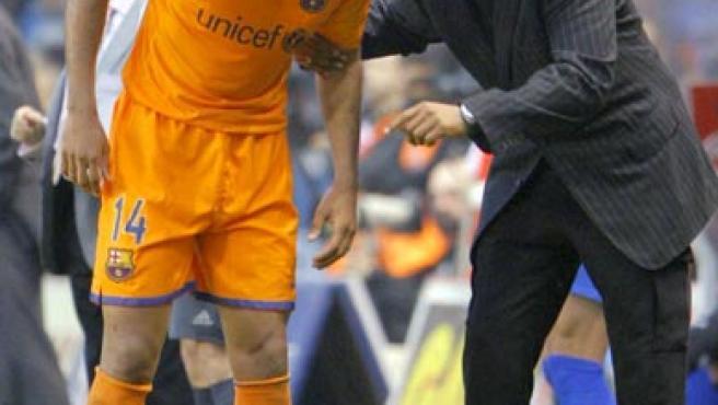 Rijkaard susurra al oído de Henry. (EFE)