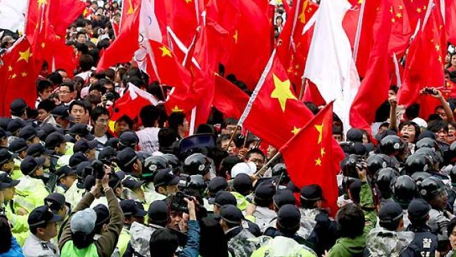 Un grupo de policías forman un cordon de seguridad delante de un grupo de simpatizantes de China. (Jeon Heon-Kyun / EFE).