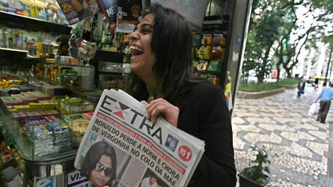 """Andreia Albertino ríe tras leer el titular de un periódico local que dice: """"Ronaldo pierde la novia y llora de vergüenza en el cuello de la madre"""". (EFE)."""