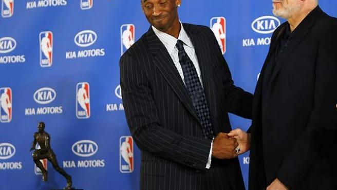 Kobe Bryant mira su trofeo MVP mientras saluda a su entrenador, Phil Jackson. (Mike Blake / Reuters).