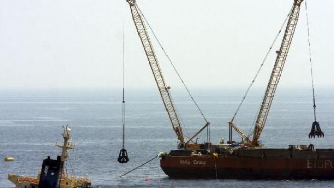 Varias grúas sacan chatarra de los depósitos del buque 'New Flame' que sigue encallado en la costa cerca de Gibraltar. (A.C.R./EFE)