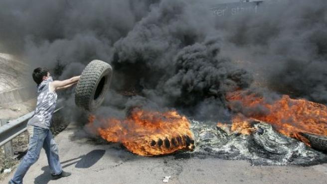 Un simpatizante de Hizbulá prende fuego a varios neumáticos en una carretera de Beirut (REUTERS).