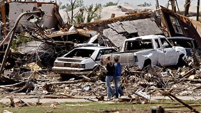 Dos personas caminan junto a los restos de una casa después de que un tornado destruyera el pueblo y matara a siete personas en Picher, Oklahoma. (Larry W. Smith / EFE).
