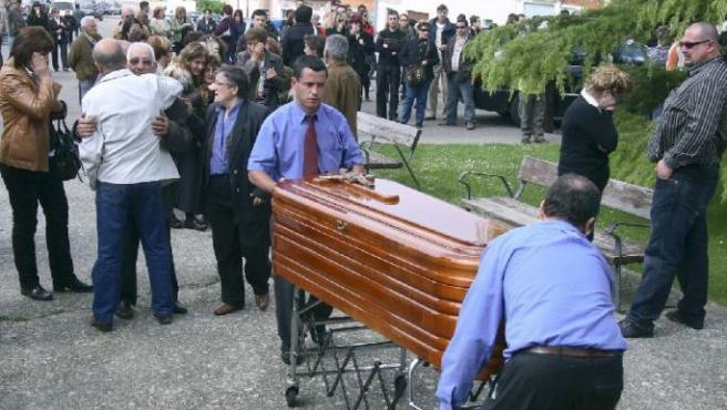 Miembros de la funeraria trasladan el cuerpo sin vida de María Jesús.