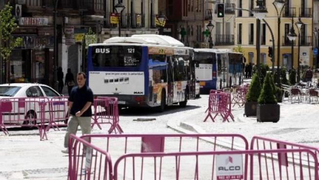 Dos autobuses y un taxi circulan por la calle Angustias.