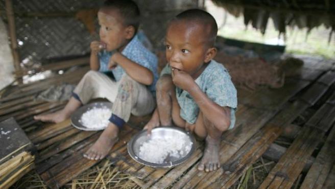 Dos hermanos comen un plato de arroz donado por la ONU en los restos de su hogar en Kundangon, Birmania (REUTERS).
