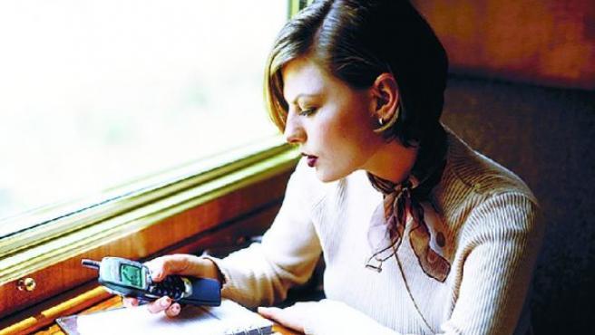 Una joven consulta su teléfono móvil.