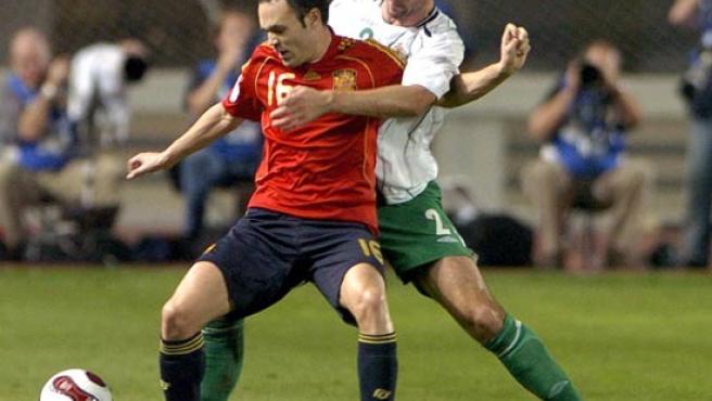 Iniesta pelea un balón con McAuley, de Irlanda del Norte (EFE).
