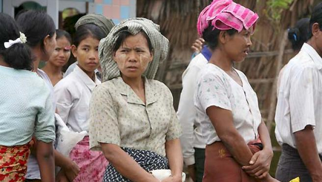 Varias personas hacen cola para coger ayuda humanitaria en la localidad de KonChanGone, en Yangon. (EFE).