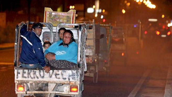 Un grupo de rumanos gitanos, escoltado por la policía, abandona su campamento en Ponticelli, en Nápoles (Italia). (Ciro Fusco / EFE).
