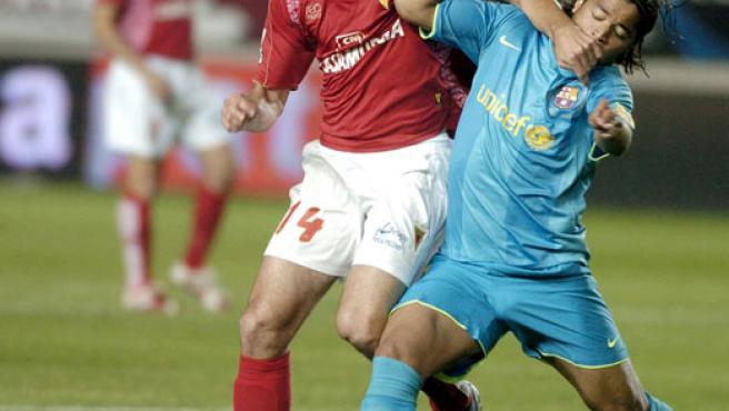 El centrocampista del Real Murcia, Álvaro Mejía (i), disputa el balón con el delantero mejicano del FC Barcelona, Giovani dos Santos (d). (EFE)