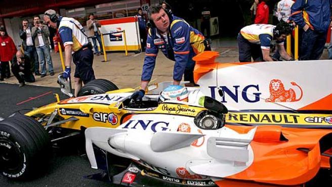 Los mecánicos de Renault empujan el R28 de Fernando Alonso.